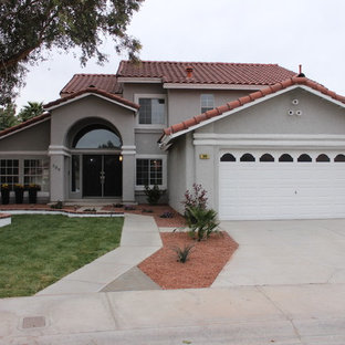Inspiration for a large mediterranean gray two-story stucco exterior home remodel in Las Vegas with a hip roof