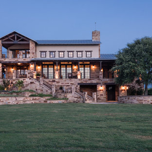 Large tuscan beige split-level stone exterior home photo in Austin with a hip roof