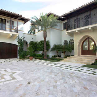 Design ideas for a mediterranean two-storey exterior in Miami with wood siding.
