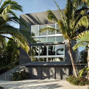 Large modern gray two-story stucco exterior home idea in Miami