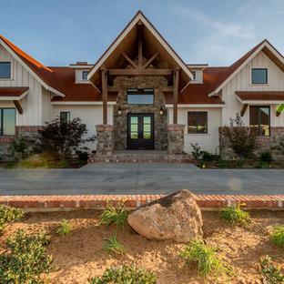 Foto de fachada de casa blanca, rústica, grande, de dos plantas, con revestimientos combinados, tejado a doble faldón y tejado de metal
