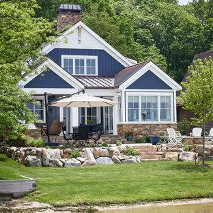 Идея дизайна: двухэтажный, синий частный загородный дом среднего размера в морском стиле с облицовкой из ЦСП, двускатной крышей и крышей из смешанных материалов