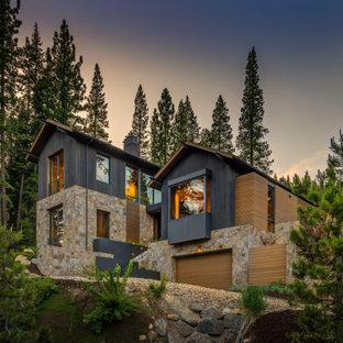 Пример оригинального дизайна: большой, трехэтажный, серый частный загородный дом в стиле модернизм с комбинированной облицовкой и двускатной крышей для охотников