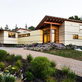 Modelo de fachada amarilla, actual, grande, a niveles, con revestimiento de aglomerado de cemento y tejado de un solo tendido