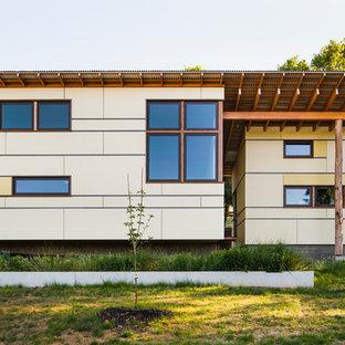 Esempio della facciata di una casa gialla contemporanea a piani sfalsati con rivestimento con lastre in cemento e tetto a una falda