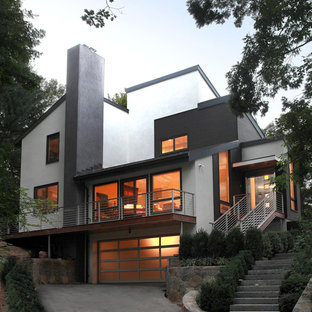 Example of a mid-sized minimalist white two-story concrete house exterior design in New York with a shed roof