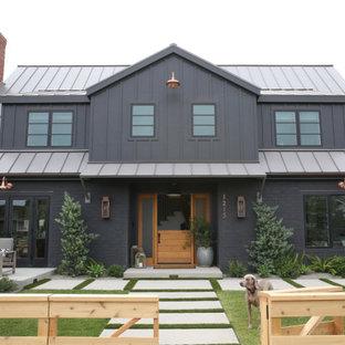 Diseño de fachada de casa negra, campestre, de dos plantas, con revestimiento de ladrillo, tejado a dos aguas y tejado de metal