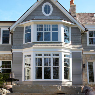 Photo of an expansive traditional two-storey grey house exterior in Chicago with mixed siding, a gable roof and a shingle roof.