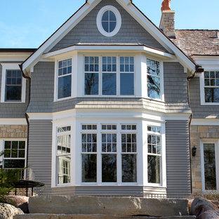 Imagen de fachada de casa gris, tradicional, extra grande, de dos plantas, con revestimientos combinados, tejado a dos aguas y tejado de teja de madera