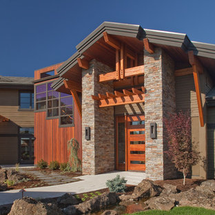 Large mountain style multicolored two-story stone exterior home photo in Portland with a shingle roof