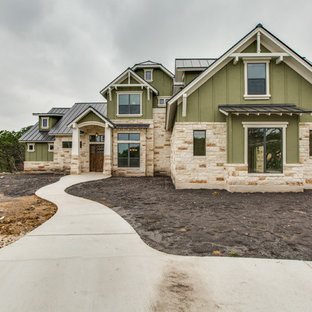 Example of a large arts and crafts green two-story stucco exterior home design in Austin