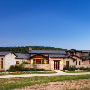 Mediterranean house exterior in Austin with stone cladding, a pitched roof and a metal roof.