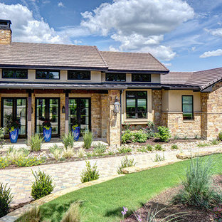 Inspiration for a huge mediterranean multicolored two-story stone exterior home remodel in Austin with a shingle roof