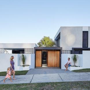 На фото: двухэтажные фасады частных домов серого цвета в стиле модернизм с комбинированной облицовкой и плоской крышей