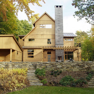 Example of a large mountain style two-story wood house exterior design in Burlington with a metal roof