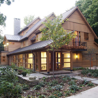 Inspiration for a large rustic beige two-story wood house exterior remodel in Burlington with a metal roof