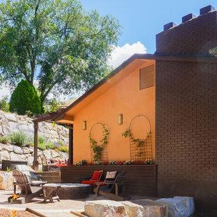 Foto de fachada de casa multicolor, bohemia, de tamaño medio, a niveles, con revestimiento de estuco, tejado a dos aguas y tejado de teja de madera