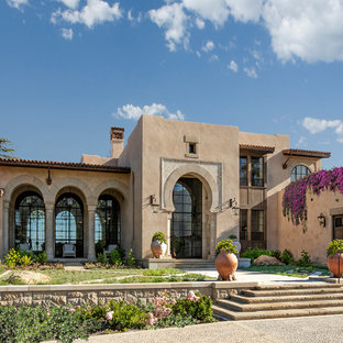 Inspiration for a mediterranean two-storey beige house exterior in Santa Barbara with a flat roof and a tile roof.