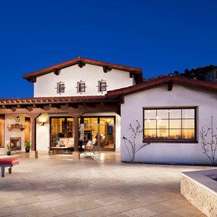 Diseño de fachada blanca, tradicional, grande, de dos plantas, con revestimiento de adobe y tejado de teja de barro