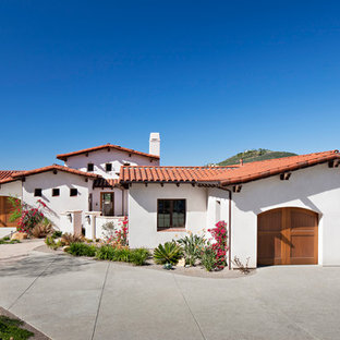 This is an example of a large mediterranean two-storey adobe white exterior in San Diego with a hip roof.