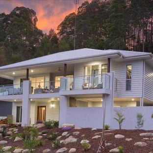 Imagen de fachada blanca, tropical, de tamaño medio, a niveles, con revestimientos combinados