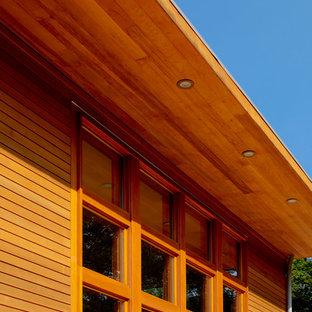 Modelo de fachada de casa multicolor, contemporánea, grande, de dos plantas, con revestimientos combinados, tejado a dos aguas y tejado de metal
