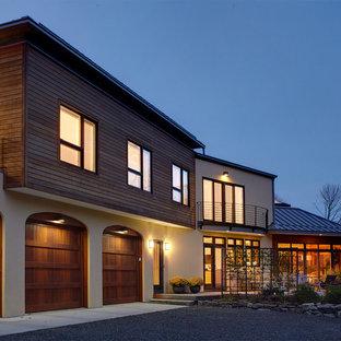 Esempio della villa grande beige contemporanea a due piani con rivestimento in legno, tetto a capanna e copertura in metallo o lamiera