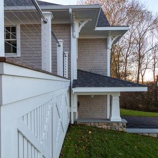 Imagen de fachada de casa beige, de estilo americano, de tamaño medio, a niveles, con revestimiento de madera, tejado a dos aguas y tejado de teja de madera