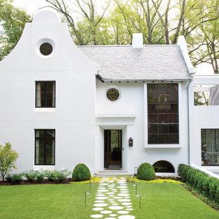 Exempel på ett mellanstort klassiskt vitt hus, med tak i shingel, två våningar, stuckatur och sadeltak
