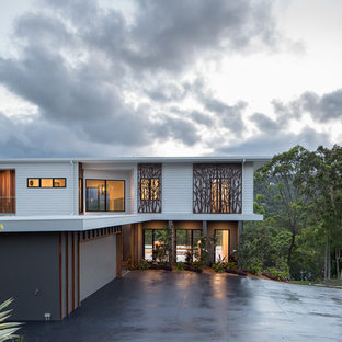 Design ideas for a large contemporary two-storey white house exterior in Gold Coast - Tweed with concrete fiberboard siding, a flat roof and a metal roof.