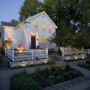 Foto della facciata di una casa piccola bianca classica a due piani con rivestimento in legno