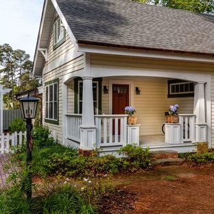 Ejemplo de fachada amarilla, de estilo de casa de campo, pequeña, de una planta, con revestimiento de madera