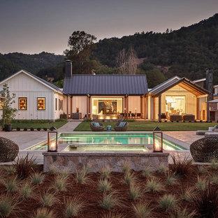Lantlig inredning av ett vitt hus, med allt i ett plan, sadeltak och tak i metall