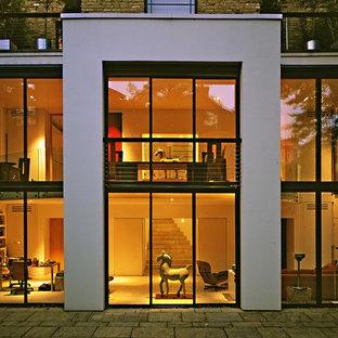 Idee per la facciata di una casa contemporanea a due piani con rivestimento in vetro