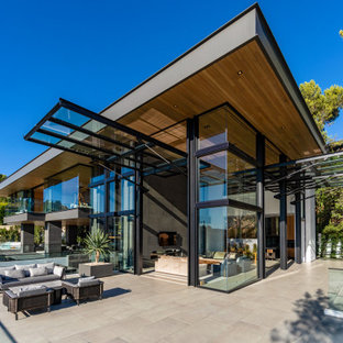 Design ideas for a contemporary glass house exterior in Orange County with a shed roof.