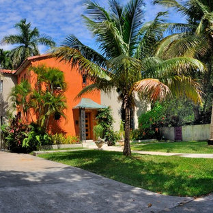 Inspiration for a tropical two-storey orange exterior in Miami.