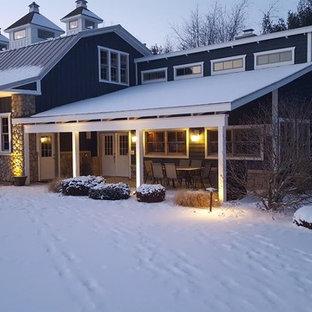 Ejemplo de fachada de casa multicolor, de estilo de casa de campo, de tamaño medio, de dos plantas, con revestimientos combinados, tejado a doble faldón y tejado de metal