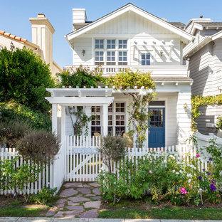 Diseño de fachada de casa blanca, marinera, de dos plantas, con tejado a dos aguas y tejado de teja de madera