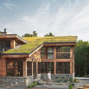Неиссякаемый источник вдохновения для домашнего уюта: большой, деревянный, коричневый дом в современном стиле с односкатной крышей и зеленой крышей
