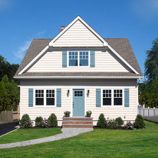 Mid-sized elegant beige two-story vinyl exterior home photo in New York with a shingle roof