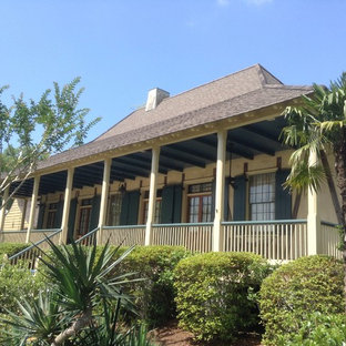 Design ideas for a mid-sized asian one-storey stucco beige house exterior in New Orleans with a hip roof and a shingle roof.