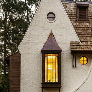Idee per la facciata di una casa bianca classica a due piani con rivestimento in mattoni e copertura a scandole
