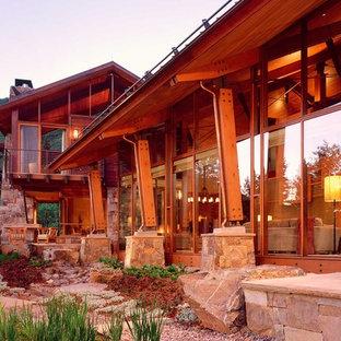 Diseño de fachada de casa rural, grande, de dos plantas, con revestimiento de piedra y tejado a dos aguas