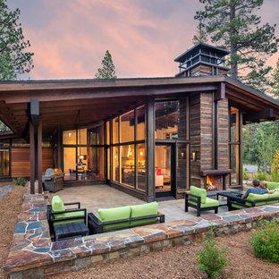 Imagen de fachada marrón, rural, de tamaño medio, de dos plantas, con revestimiento de madera y tejado a dos aguas