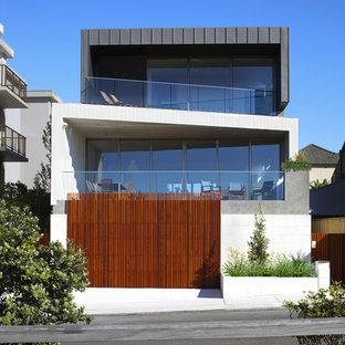 Imagen de fachada minimalista, grande, de tres plantas, con revestimientos combinados y tejado plano