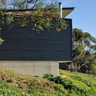 Ejemplo de fachada azul, contemporánea, de tamaño medio, de una planta, con revestimiento de metal y tejado plano