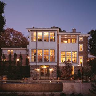 Aménagement d'une très grand façade de maison multicolore classique à deux étages et plus avec un toit à quatre pans et un revêtement mixte.