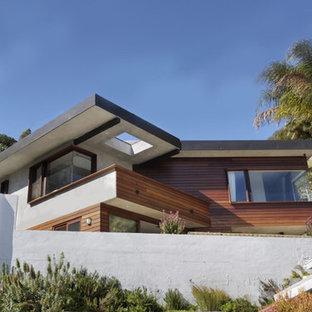 ロサンゼルスのコンテンポラリースタイルのおしゃれな家の外観 (漆喰サイディング、グレーの外壁、半切妻屋根) の写真