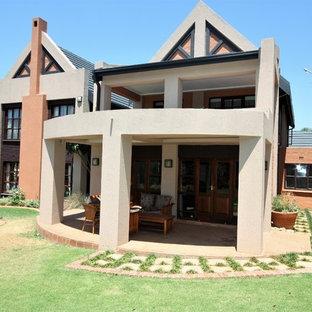 Modelo de fachada de casa blanca, ecléctica, de tamaño medio, de dos plantas, con revestimiento de hormigón, tejado a dos aguas y tejado de teja de barro