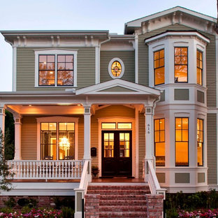 ヒューストンの中くらいのヴィクトリアン調のおしゃれな二階建ての家 (木材サイディング、緑の外壁) の写真